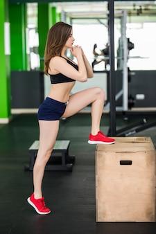 Frau in kurzer moderner kleidung arbeitet mit step-box-sport-simulator im fitnessstudio