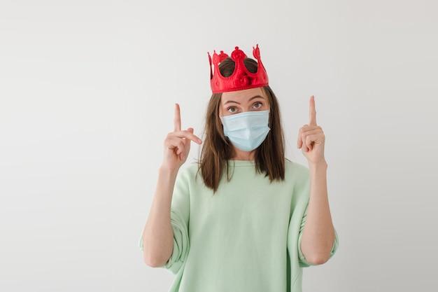 Frau in maske und krone zeigt nach oben
