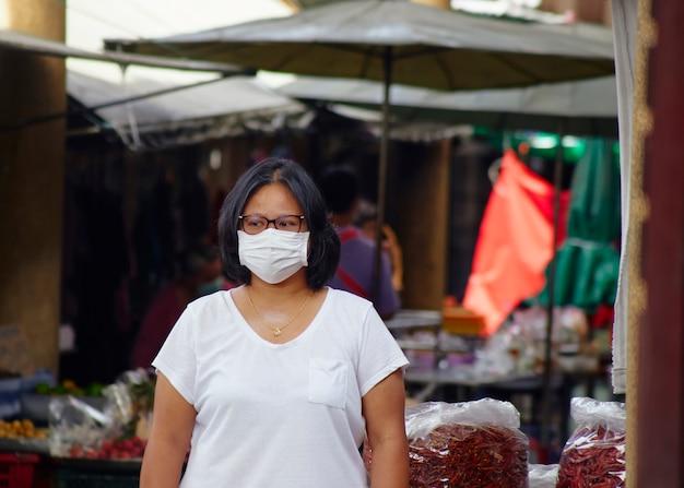 Frau in masken zum schutz vor viren und grippe auf belebten marktstraßen