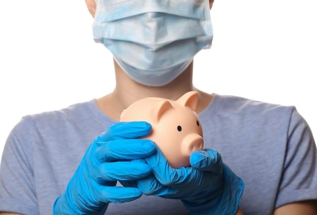Frau in medienmaske und handschuhen hält sparschwein isoliert auf weiß