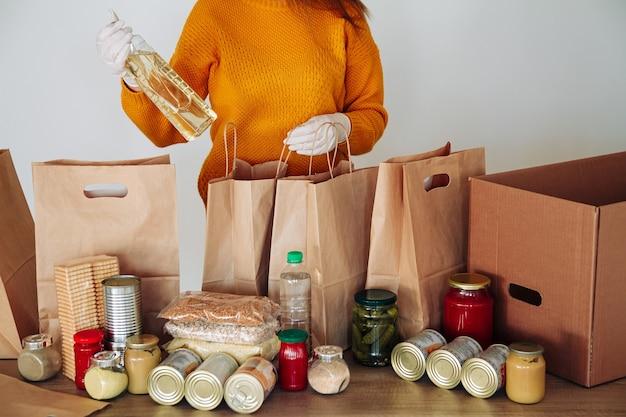 Frau in medizinischen handschuhen, die lebensmittel für spende verpacken