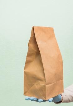 Frau in medizinischen schutzhandschuhen liefert essen zum mitnehmen. lieferservice unter quarantäne