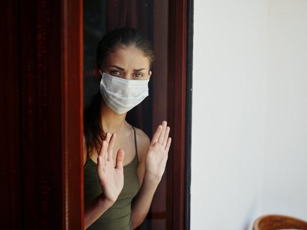 Frau in medizinischer maske, die aus dem fenster quarantäneverbot schaut