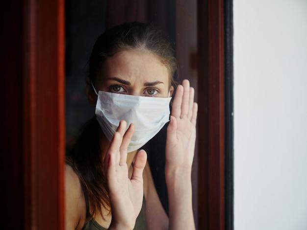 Frau in medizinischer maske, die aus dem fenster schaut, trauriger ausdruck, sperrung