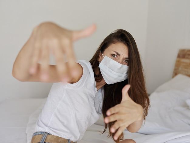 Frau in medizinischer maske, die mit ihren händen gestikuliert, während sie auf einem pandemie-coronavirus-urlaub im bett sitzt