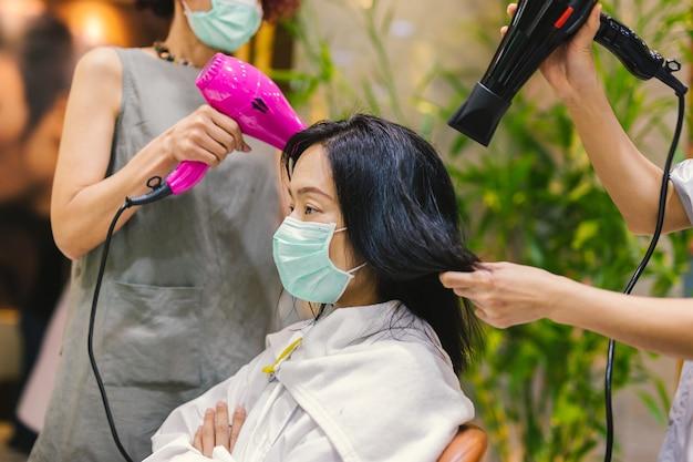 Frau in medizinischer maske, die sich im friseursalon die haare trocknen lässt