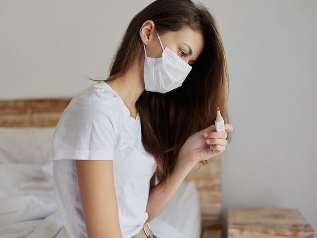 Frau in medizinischer maske, die thermometer im schlafzimmer betrachtet