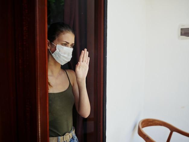 Frau in medizinischer maske, die traurig aus dem fenster schaut