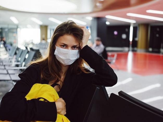 Frau in medizinischer maske hält die hand auf dem kopf des gelben rucksack-flughafenpassagieres
