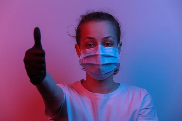 Frau in medizinischer maske und handschuhen zeigt daumen nach oben. rot-blaues neonlicht mit farbverlauf