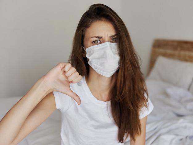 Frau in medizinischer maske zeigt daumen nach unten auf dem bett