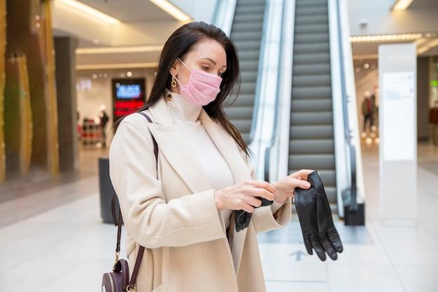 Frau in medizinischer maske zieht schwarze lederhandschuhe im einkaufszentrum oder flughafen an