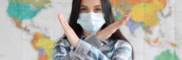 Frau in medizinischer schutzmaske, die eine verbietende geste vor dem hintergrund der weltkarte zeigt
