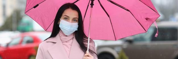 Frau in medizinischer schutzmaske, die regenschirm in den händen hält, neue realität während der covid-pandemie