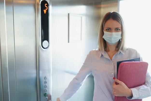 Frau in medizinischer schutzmaske drückt den knopf in der gesundheitssicherheit des aufzugs an öffentlichen orten