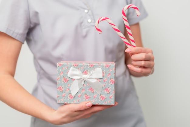 Frau in medizinischer uniform mit geschenkbox und weihnachtssüßigkeit
