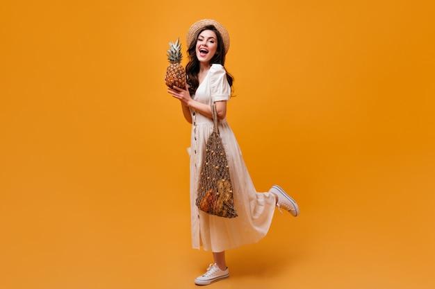 Frau in midikleid, hut und turnschuhen hält einkaufstasche und ananas auf orange hintergrund.
