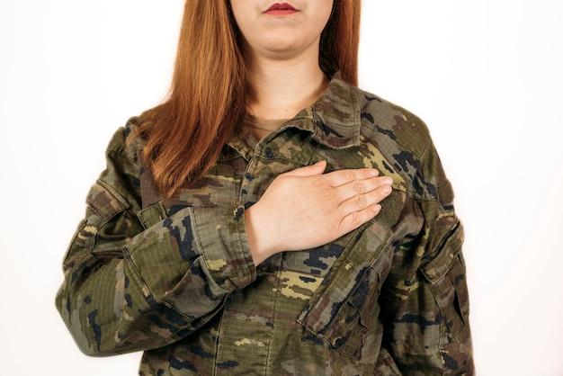Frau in militärischer tarnung stehend mit ihrer hand auf ihrem herzen