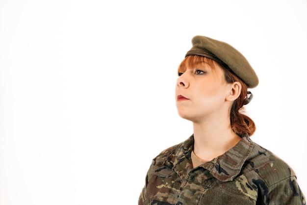 Frau in militärischer tarnung und einem hut, der stolz steht