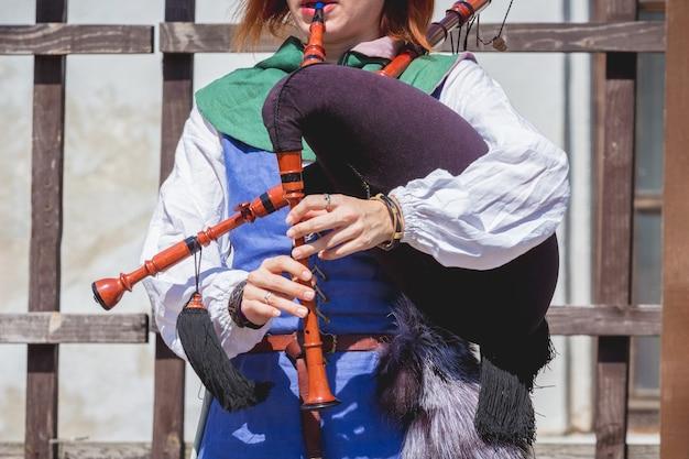 Frau in mittelalterlichen kleidern, die auf einem dudelsack spielen