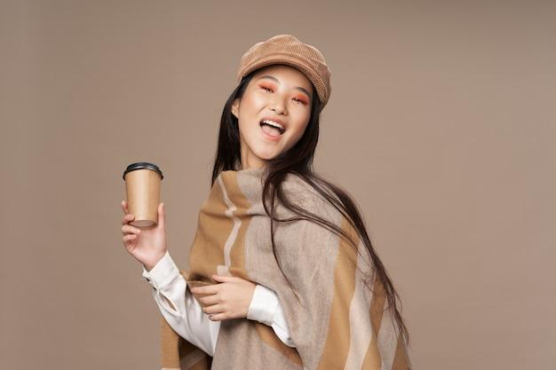 Frau in modischer kleidung mit einer tasse kaffee in der hand und modischem hut