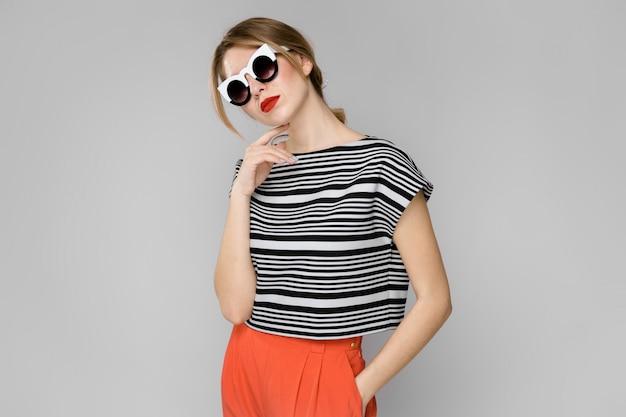 Frau in modischer kleidung und sonnenbrille