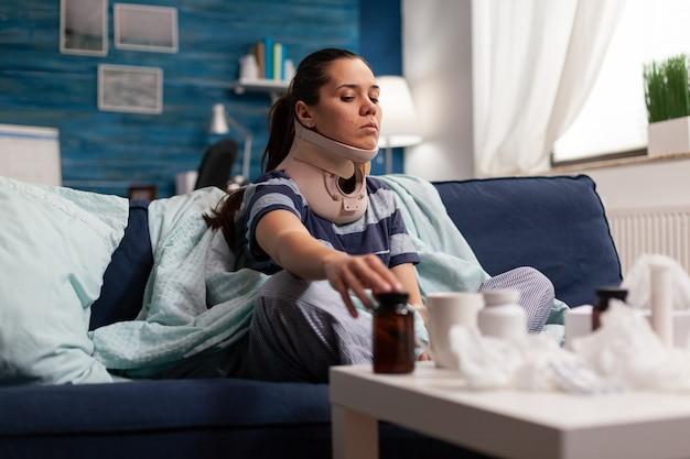 Frau in nackenstütze leidet unter schmerzen auf sofa