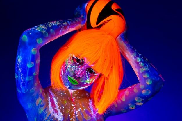 Frau in neon make-up hält einen fußball in ihren händen. konzept der weltmeisterschaft. fluoreszierende farbe in uv-licht