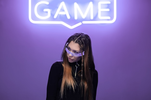 Frau in neonbrille in einem neonraum mit neonspielzeichen. hochwertiges foto