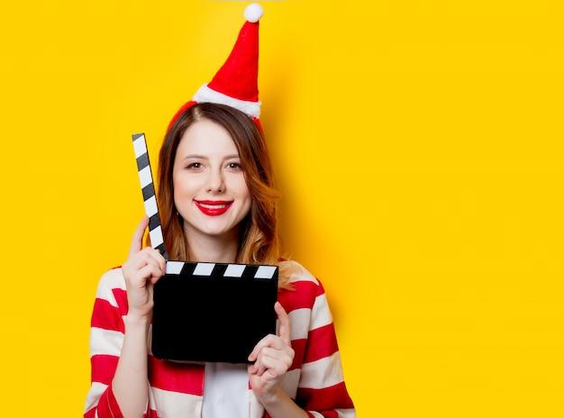 Frau in nikolausmütze mit filmklappe