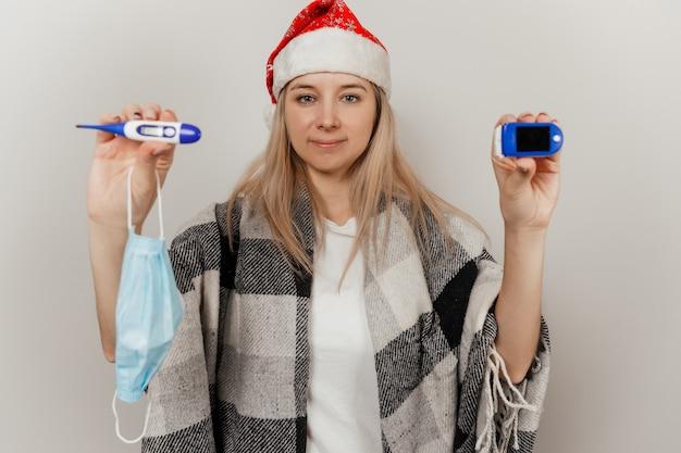 Frau in nikolausmütze und medizinischer schutzmaske hält thermometer und pulsoximeter