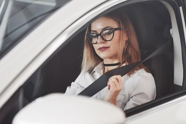 Frau in offiziellen kleidern, die ihr neues auto im autosalon versuchen
