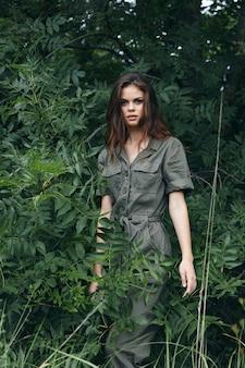 Frau in overalls im park in der nähe der büsche im freien beschnittene bäume