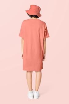 Frau in pfirsichfarbenem t-shirt-kleid und freizeitkleidung mit fischerhut