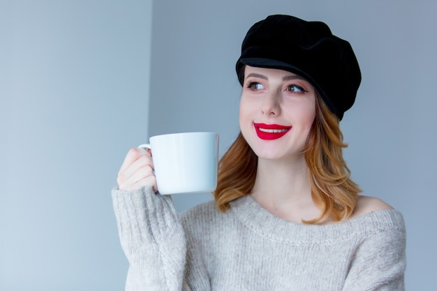 Frau in pullover und hut mit tasse kaffee oder tee