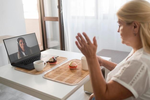 Frau in quarantäne, die einen drink mit freunden auf laptop hat