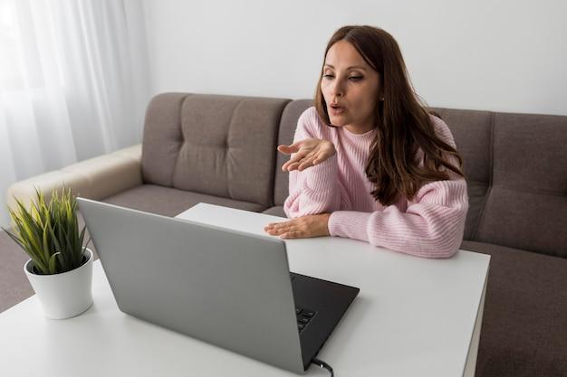 Frau in quarantäne, die küsse zu leuten auf laptop bläst