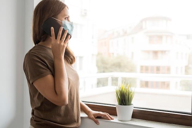 Frau in quarantäne zu hause, die am telefon spricht, während sie durch das fenster schaut