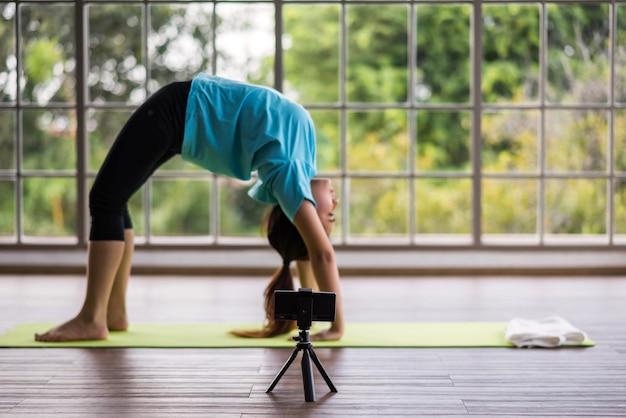 Frau in radpose für online-yoga-kurs zu hause