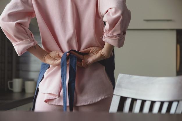 Frau in rosa anzug bindet blaue schürze auf dem rücken, um in ihrer heimischen küche zu kochen gesichtsloses bild