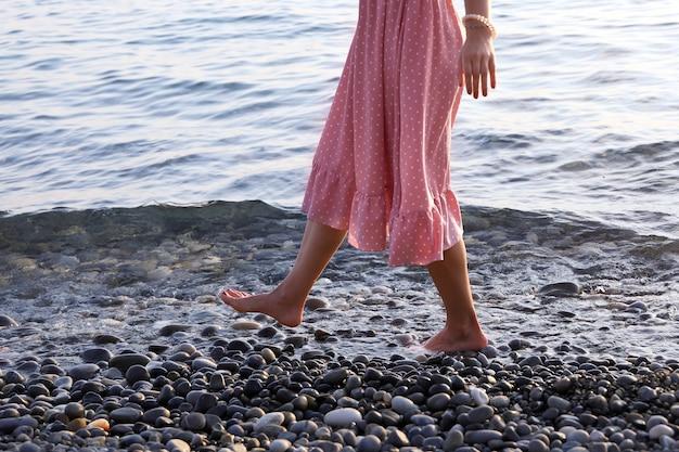 Frau in rosa kleid geht barfuß am rand des wassers an der küste