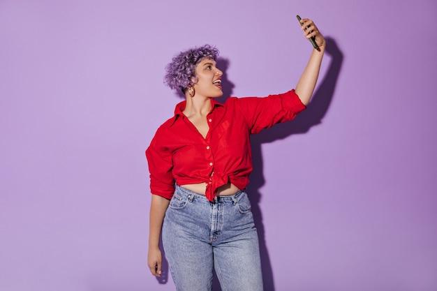 Frau in rotem langarmhemd und eng anliegender jeans nimmt selfie auf. nette frau mit stilvollem haarschnitt, der aufwirft.