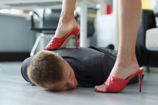Frau in roten schuhen, die auf den kopf eines jungen mannes im anzug im büro tritt