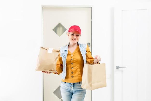 Frau in roter mütze, die fast-food-bestellung nach hause gibt. weiblicher kurier, der papierpaket mit nahrung hält. lieferung der produkte vom geschäft oder restaurant nach hause. platz kopieren