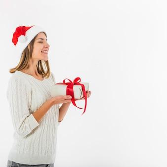 Frau in sankt-hut, der mit geschenkbox steht