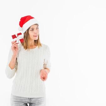 Frau in Sankt-Hut, der rote Geschenkbox nahe Ohr hält