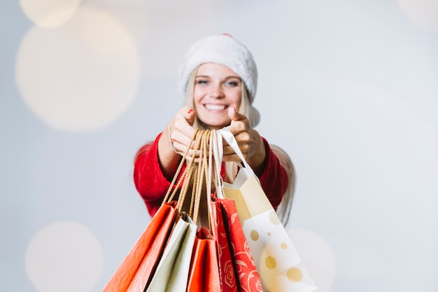 Frau in sankt-hut mit einkaufstaschen
