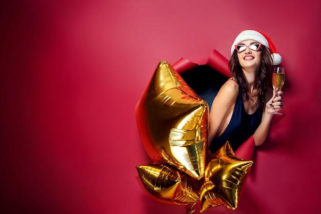 Frau in santaat hält goldene luftballons