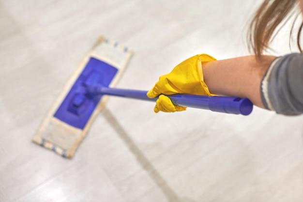 Frau in schützenden gelben gummihandschuhen mit flachem nassem mopp beim putzen des zimmers