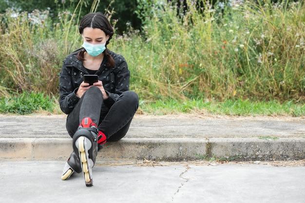 Frau in schützender gesichtsmaske, auf rollschuhpause, sitzend auf der straße und unter verwendung des mobiltelefons während des ausbruchs der coronavirus-pandemie. urban girl telefoniert mit rollschuhen.